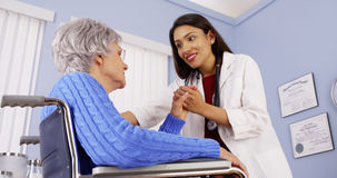 Mexican woman doctor comforting elderly patient Stock Images