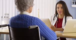 Mexican woman doctor talking with elderly patient Royalty Free Stock Image