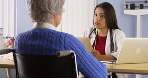 Mexican woman doctor talking with senior patient Stock Photo