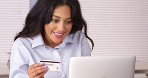 Mexican woman happily making purchase over the phone Royalty Free Stock Images