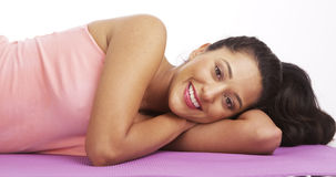 Mexican woman lying on yoga matt smiling Stock Image
