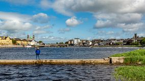 Mexican woman posing in the small pier of the river Shannon. With calm waters in the village of Athlone in the background, wonderful spring day in the county of royalty free stock photo