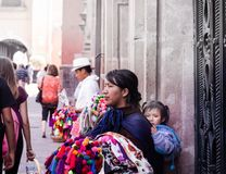 Mexican woman selling handcrafts. QUERETARO, QUERETARO / MEXICO - 06 22 2017: Mexican woman with traditional dress selling handcrafts royalty free stock photos