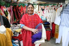 Mexican woman selling traditional mexican shawl and  clothes in Royalty Free Stock Images