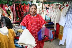 Mexican woman selling traditional mexican shawl and  clothes in Stock Photo