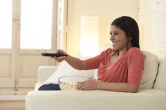 Mexican woman watching television at sofa couch happy excited enjoying romantic film Royalty Free Stock Photo