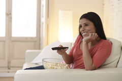 Mexican woman watching television at sofa couch happy excited enjoying romantic film Royalty Free Stock Images