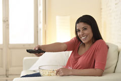 Mexican woman watching television at sofa couch happy excited enjoying romantic film Stock Photos