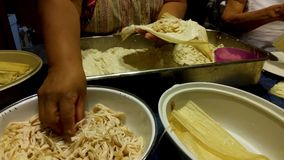 Mexican women are making homemade tamales. Mexican food. Mexican women prepare and make homemade green tamales with chicken filling. Mexican food stock footage
