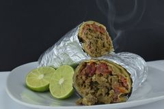 Mexican wrapped burrito and lemon royalty free stock photo