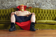 Mexican wrestler sitting on a couch. Photograph of a Mexican wrestler or Luchador sitting on a green couch waiting for his match to begin Royalty Free Stock Photos