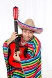 Mexicano divertido con la guitarra aislada en blanco fotos de archivo