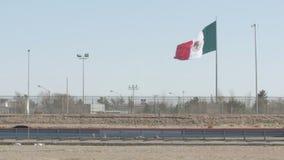 Mexicansk flagga som vinkar nära USA och den Mexico gränsen och huvudvägen arkivfilmer