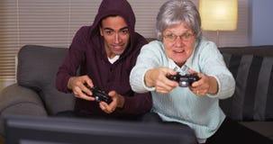Mexicansk grabb som spelar videospel med mormodern royaltyfria foton