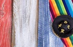 Mexicansk partihatt och serape på målade lantliga träbräden in royaltyfria bilder