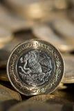 Mexicansk valuta i förgrunden, med många mer mynt i bakgrunden Arkivfoton