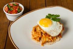 Mexicanska frukostchilaquiles med bönor och det stekte ägget överst, med nya pico de gallo arkivbild