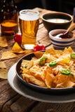 Mexicanska nachos tjänade som med ost, variation av dopp, öl som var kyligt, tomater, lantlig trätabell royaltyfria foton