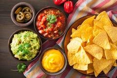 Mexicanska nachostortillachiper med guacamole, salsa och ost D royaltyfria bilder