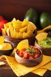 Mexicanska nachostortillachiper med guacamole, salsa och ost D royaltyfri fotografi
