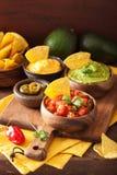 Mexicanska nachostortillachiper med guacamole, salsa och ost D royaltyfria foton