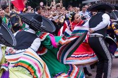 Mexicanska pojkar och flickor i traditionell färgrik folkdräkt dansar på festivalen Arkivfoto