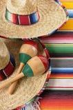 Mexicanska sombrero med maracas och traditionella serapefiltar Royaltyfri Bild