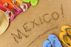 Mexico, Mexican beach sand word writing. Mexico beach background with towel and flip flops Royalty Free Stock Photos