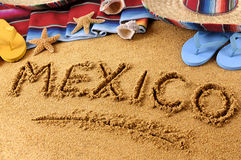 Mexico summer beach writing sign. The word Mexico written in sand on a Mexican beach, with sombrero, straw hat, traditional serape blanket, starfish and Stock Photo