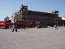 Facade of representative historical buildings in Mexico City at famous Zocalo main square and red buses stock photos