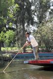 Mexico City. A Trajinera boat driver pushes a boat down the canal at Xochimilco on March 21, 2014 in Mexico City Royalty Free Stock Image