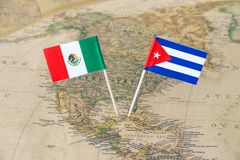 Mexico and Cuba flag pins on a world map, political relations concept Royalty Free Stock Images
