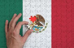 Mexico flag is depicted on a puzzle, which the man`s hand completes to fold.  stock illustration