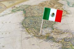 Mexico flag pin on map. Paper flag pin of Mexico on a map showing neigbouring countries. Officially the United Mexican States is a federal republic in the Stock Image
