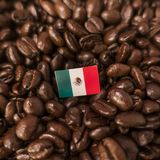 A Mexico flag placed over roasted coffee beans royalty free stock photos