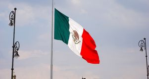 Mexico flag. Waving mexican flag at the center of the country in the mexico city main plaza, green white and red flag hanging in a metallic post, waving with the stock image