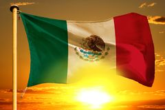 Mexico flag weaving on the beautiful orange sunset with clouds background. Mexico flag weaving on the beautiful orange sunset background royalty free stock images