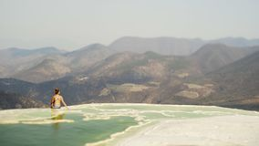 Mexico Hierve el Agua. Beautiful view with young girl sitting on the brink of mineral  pool, Mexico Hierve el Agua stock video footage
