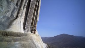Mexico Hierve el Agua. Young women walking near calcium stalagmite, dres and hair flapping on the wind, Mexico Hierve el Agua stock video footage