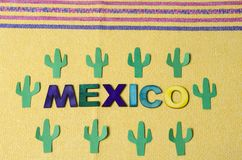 Mexico made from colorful wooden letters and paper green cactus. With little pink flowers on yellow tablecloth