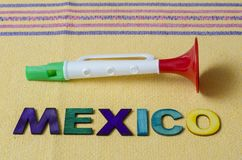 Mexico made from colorful wooden letters and toy trumpet. On yellow tablecloth