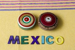 Mexico made from colorful wooden letters and wooden retro yoyos. On yellow tablecloth