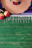 Mexico mexican sombrero maracas fiesta green old wood background vertical stock photo