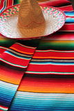 Poncho sombrero Mexican Mexico cinco de mayo rug poncho fiesta background with stripes. Poncho sombrero Mexico traditional cinco de mayo rug poncho fiesta stock photo