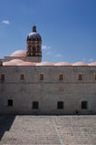 Mexico Oaxaca Santo Domingo monastery courtyard view with church. Tower and sitting figure Stock Photo
