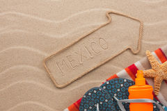 Mexico pointer and beach accessories lying on the sand. As background Stock Images