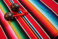 Mexico poncho serape maracas Mexican traditional cinco de mayo rug poncho fiesta background with stripes. Mexico poncho serape  traditional cinco de mayo rug Royalty Free Stock Images