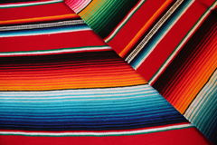 Mexico poncho serape maracas Mexican traditional cinco de mayo rug poncho fiesta background with stripes. Mexico poncho serape  traditional cinco de mayo rug Stock Photo