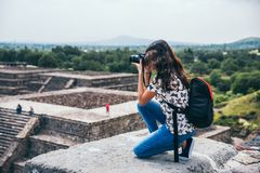 MEXICO - SEPTEMBER 21: Girl kneeling to take a picture of the landscape from the Pyramid of the moon. September 21, 2017 in Teotihuacan, Mexico Royalty Free Stock Photography