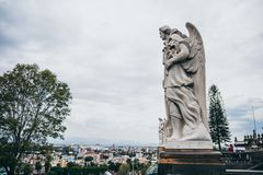 MEXICO - SEPTEMBER 20: Guardian angel statues located at the Tepeyac hills and cityscape in the background royalty free stock image